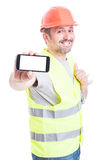 Smiling handsome builder holding phone and thumb up Stock Image