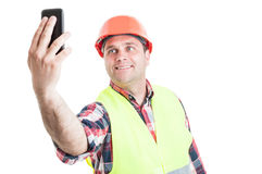 Smiling handsome builder making self portrait. With cellphone on white background Stock Image
