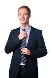Smiling handsome businessman editing his tie Royalty Free Stock Image