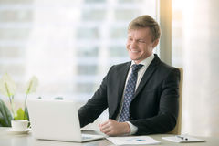 Smiling handsome businessman with laptop Royalty Free Stock Photos