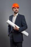 Smiling handsome businessman in orange helmet with blueprint Stock Photo