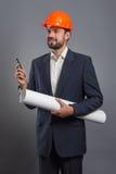 Smiling handsome businessman in orange helmet with blueprint Royalty Free Stock Photo
