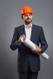 Smiling handsome businessman in orange helmet with blueprint Stock Images