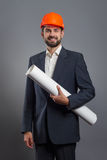 Smiling handsome businessman in orange helmet with blueprint Royalty Free Stock Photography