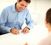 Smiling handsome businessman sign a contract Royalty Free Stock Photo