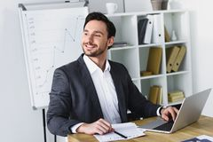 Smiling handsome businessman sitting at table and looking away. In office stock photo