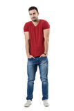 Smiling handsome casual man with hands in pockets looking at camera. Full body length portrait isolated over white studio background Royalty Free Stock Image