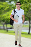 Smiling handsome college student walking by at college park with Stock Photo