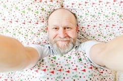 Smiling handsome elderly man. Resting on the bed Stock Images