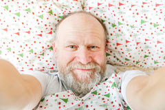 Smiling handsome elderly man. Resting on the bed Royalty Free Stock Photo