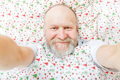 Smiling handsome elderly man. Resting on the bed Stock Photos