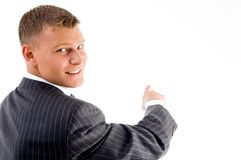 Smiling handsome employee pointing back Royalty Free Stock Photography