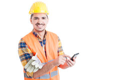 Smiling handsome engineer typing a message on modern cellphone Stock Image