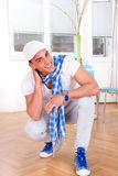 Smiling handsome fashion man with a scarf and white cap Stock Images