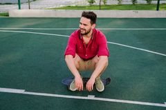 Smiling handsome fashionable guy dressed in a red shirt and shorts sitting on a skateboard on basketball court, looking away. Smiling handsome fashionable guy royalty free stock images