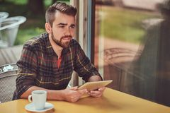 A handsome fashionable male freelancer with stylish haircut and beard, wearing fleece shirt, working on a tablet. A smiling handsome fashionable male freelancer Royalty Free Stock Photography