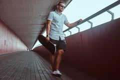 Smiling handsome fashionable skater guy in sunglasses dressed in a white shirt and shorts, leaning against a wall while. Standing on a footpath under a bridge stock photos
