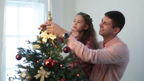 Cute girl putting decorative star on xmas tree top stock video