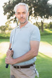 Smiling handsome golfer looking at camera Royalty Free Stock Photography