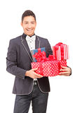 A smiling handsome guy with bow tie holding presents Stock Photos