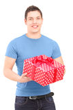 Smiling handsome guy holding a present Royalty Free Stock Images