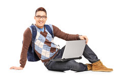 Smiling handsome guy sitting on a floor with laptop and looking Stock Images