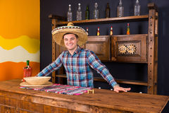 Smiling handsome male bartender in a sombrero standing at the co. Unter in Mexican pub, a shelf with spicy sauces in the background royalty free stock images