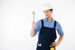 Smiling handsome male builder holding wrench. Smiling male handsome builder holding wrench isolated on a white background Royalty Free Stock Photo