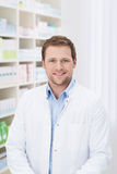 Smiling handsome male pharmacist. Standing in the pharmacy in his white coat Stock Photo