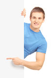 A smiling handsome male posing behind a white panel and pointing Royalty Free Stock Images