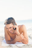 Smiling handsome man on the beach on the phone Stock Image