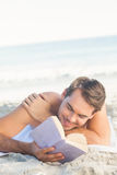 Smiling handsome man on the beach reading Stock Image