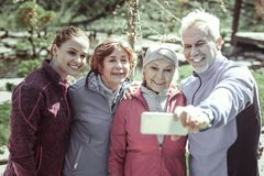Smiling handsome man doing selfie with mates. Doing selfie. Smiling handsome man doing selfie with mates after hard work out in park royalty free stock photography