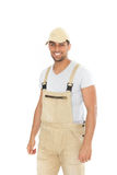 Smiling handsome man in dungarees and cap Stock Images