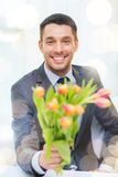Smiling handsome man giving bouquet of flowers Stock Photography