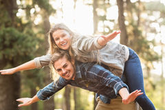 Smiling handsome man giving piggy back to his girlfriend Royalty Free Stock Photos
