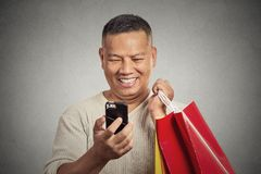 Smiling handsome man holding red shopping bags looking at his smartphone Royalty Free Stock Image