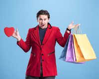 Smiling handsome man holding shopping bags and red heart Royalty Free Stock Photography