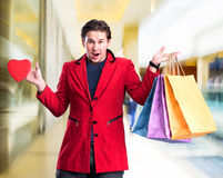Smiling handsome man holding shopping bags and red heart Royalty Free Stock Photos
