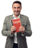 Smiling handsome man holds English textbook Royalty Free Stock Image