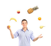 Smiling handsome man juggling fruits Stock Image