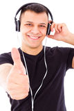 Smiling handsome man listening to music showing thumbs up Stock Photos