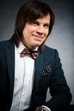 Smiling handsome man with long hair brunette and brown eyes in d. Ark suit with stripes and bow tie sitting and looking forward at black background Royalty Free Stock Photos