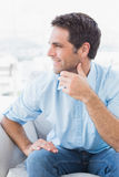 Smiling handsome man looking away on the couch Stock Images
