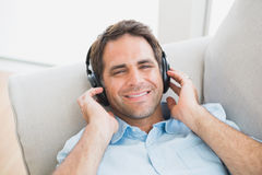 Smiling handsome man lying on sofa listening to music looking at camera Royalty Free Stock Image