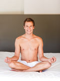Smiling handsome man meditating on bed Stock Photo