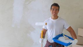 Smiling handsome man painting wall by roller at home. Repair, building and home concept.  stock video
