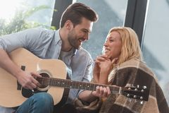 Smiling handsome man playing guitar for girlfriend. At home stock photo