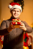 Smiling handsome man in santa hat holding red gift box Royalty Free Stock Images