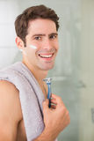 Smiling handsome man shaving in bathroom. Side view portrait of a smiling handsome young man shaving in the bathroom Stock Image